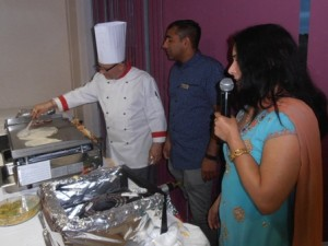 Rotarian Maya Vansia commentates for the guests as President Dipan Bhagalia learns from chef Ram how to make dosas