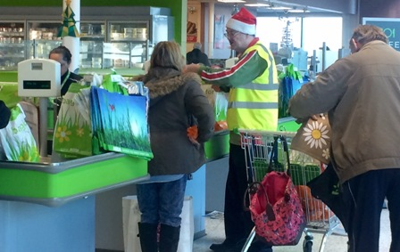 One of Santa's little helpers helps an Asda shopper pack her bags