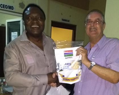 Rotary Club of Brusubi President Sapard Kalala presents a banner to Rtn Jim