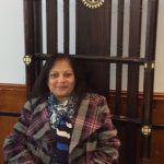 Sarita Shah sits in the ornamented chair of the President of the Rotary Club of Leicester