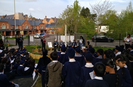 Falcons Primary School children look on as Rotary members sit in the Peace Garden