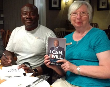 Novus Rotarian Mark Esho signs a copy of his book with Novus secretary Pam spokes holding another copy