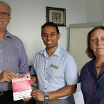 Wheels For All chairman Peter Simmonds and secretary Linda Goddard present fliers to Rotary president Jason Chauhan