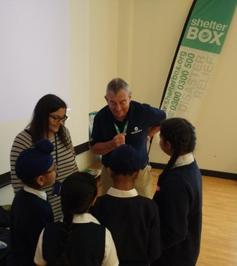 Rtn Alan Jones shows teacher Miss Krishna Popat and some of her Year 3 class some of the items included in the Shelterbox box