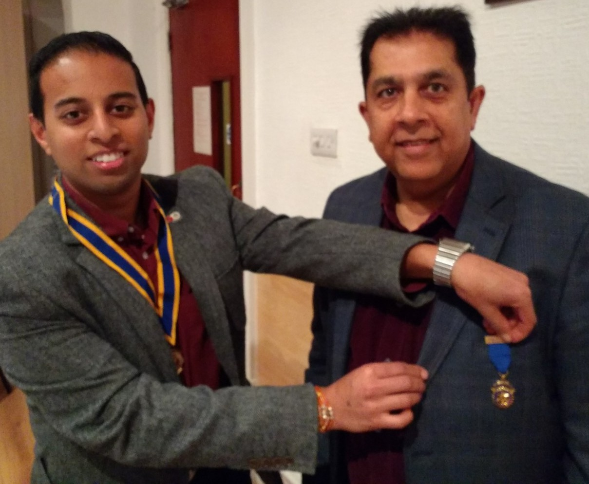 Out with the old. Pradeep Popat receives his past president's badge from Jason Chauhan