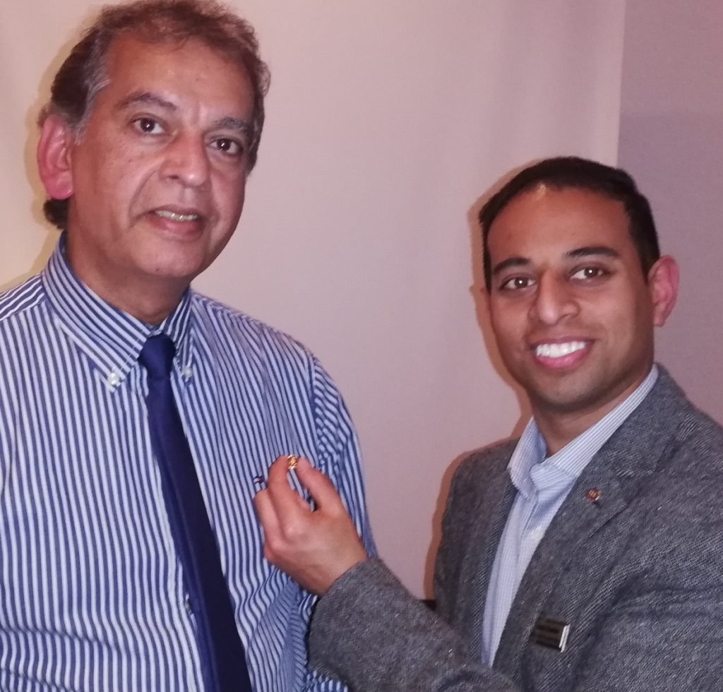 New member Ranjit Singh Mann receives his Rotary lapel badge from president Jason Chauhan
