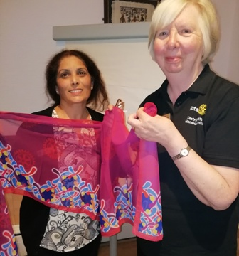 "Incoming president Maya Vansia receives a scarf from secretary Pam Spokes. The scarf bears the logo of the theme for 2019-2020 ""Rotary Connects The World"""
