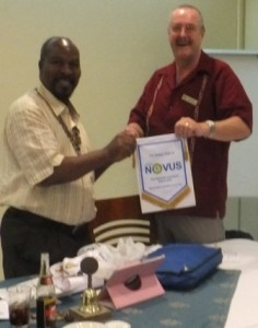 Chief Paul Odimmegwa, President of the Rotary Club of Banjul, receives a Novus banner from Jim Matthews