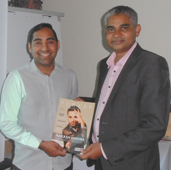 President Dipan Bhagalia receives from Romail Gulzar the most recent issue of Pukaar magazine
