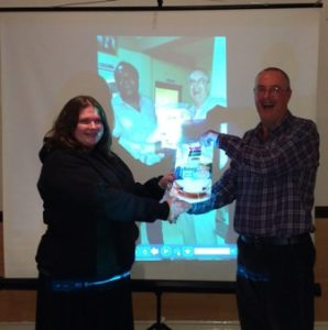 Jim Matthews presents a banner from the Rotary Club of Brusubi to President Gemma Kiddy in front of a photo of Jim receiving it in The Gambia