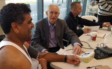 A shopper has his blood pressure measured by Prof Bert Thurston, a member of the Rotary Club of Leicester Novus