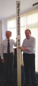 Rotarian John Niblett, of the Rotary Club of Oadby Launde, presents the Rotary Peace Pole to Frazer Robson, of the Rotary Club of Leicester Novus