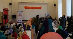 Children singing in the school hall alongside the holy Guru Granth Sahib. Please click on the photo and turn your volume up