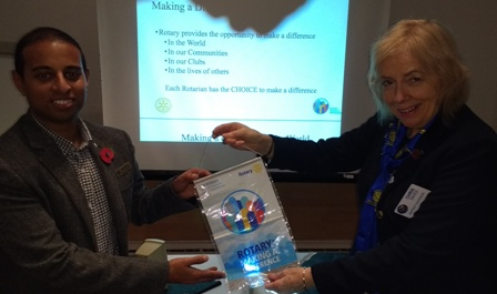 District Governor Chris Davies presents her Making A Difference banner to Novus President Elect Jason Chauhan