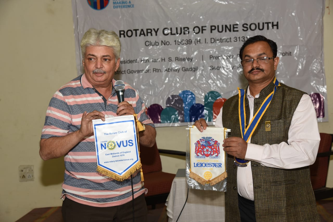 Rtn Viren Shah presents to Kiran Purohit, president of the Rotary Club of Pune the banners of the Rotary Club of Leicester and the Rotary Club of Leicester Novus which he received when he visited Novus