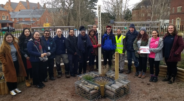 Head teacher and Novus Rotary member Jasbir Mann holds the Peace Pole with the hedge-planting volunteers