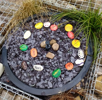 Peace. Unity. Warm. Love. Health. Some of the stones painted with words pupils say sum up the meaning of Peace. The stones were placed in the water feature of the Rotary Peace Garden