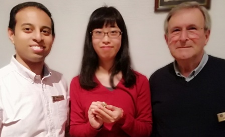 Mai Tsumura holds her pin presented to her by Rotarian John Saunders and Novus president Jason Chauhan