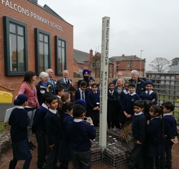 Falcons Primary School pupils showing RIBI staff, governor and Rotarians the Peace Pole which is the centrepiece of the Peace Garden
