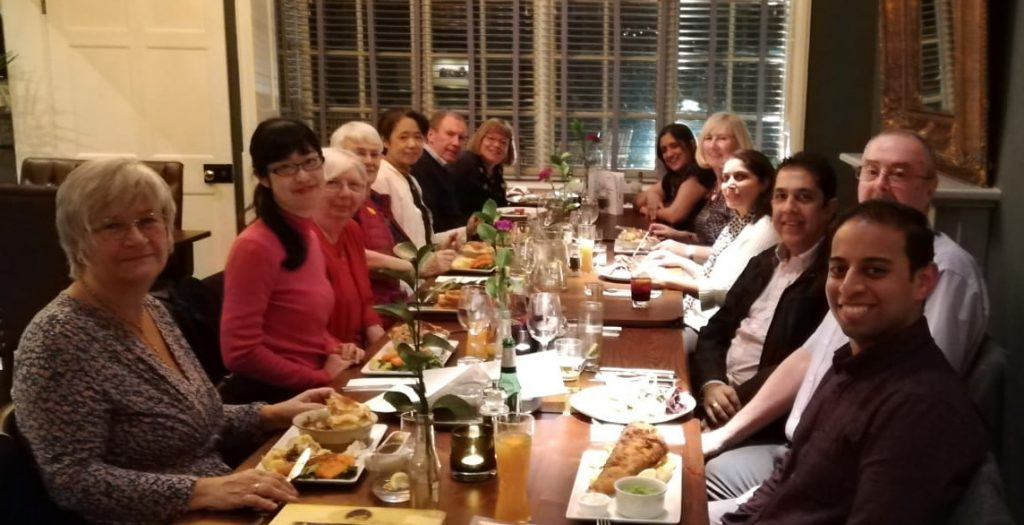 Mai Tsumura and her mother seated  with members and guests of the Rotary Club of Leicester Novus around a dining table