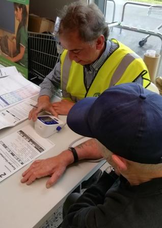Volunteer Ranjit Mann records the blood pressure of an Asda shopper